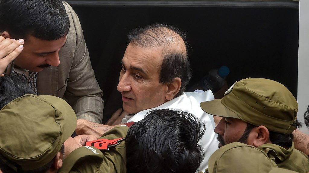 Police officials escort arrested Mir Shakeel-ur-Rehman (top) the editor-in-chief of the Jang Group, accused of scoring illegal concessions in the purchase of plots in the city, outside National Accountability Bureau (NAB) court in Lahore on March 13, 2020. - Pakistani authorities arrested a media mogul on corruption charges on March 12, in a decades-old case his representatives said was motivated by a desire to retaliate following the broadcast of several investigative programmes. (Photo by Arif ALI / AFP) (Photo by ARIF ALI/AFP via Getty Images)